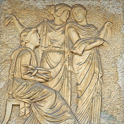 Três alegorias femininas trazem produtos agrícolas nos braços.
